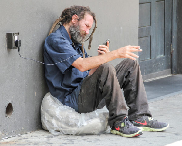 homeless man using cell phone