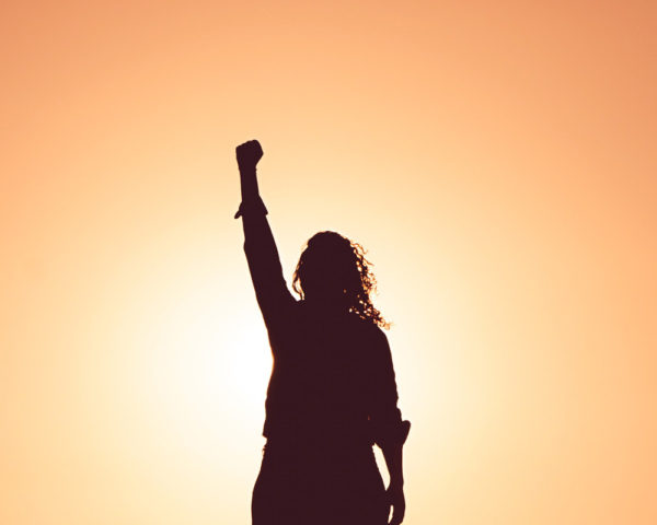 woman putting fist in air victoriously