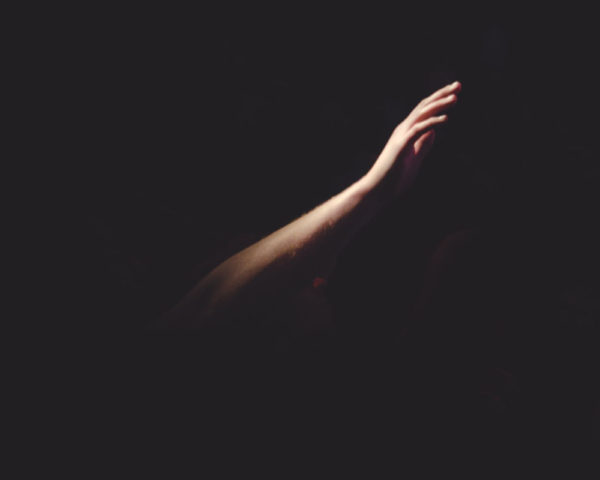 arm reaching out from the dark into the light