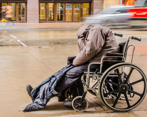Disabled homeless person sleeps on the street