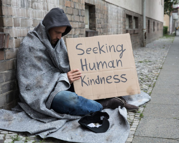 seeking human kindness sign held by homeless man