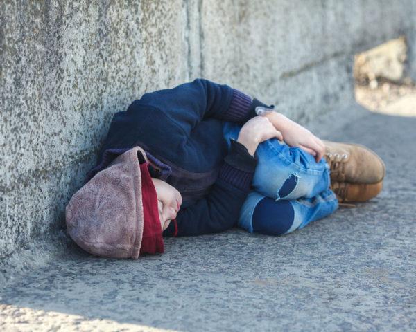 boy sleeping on concrete