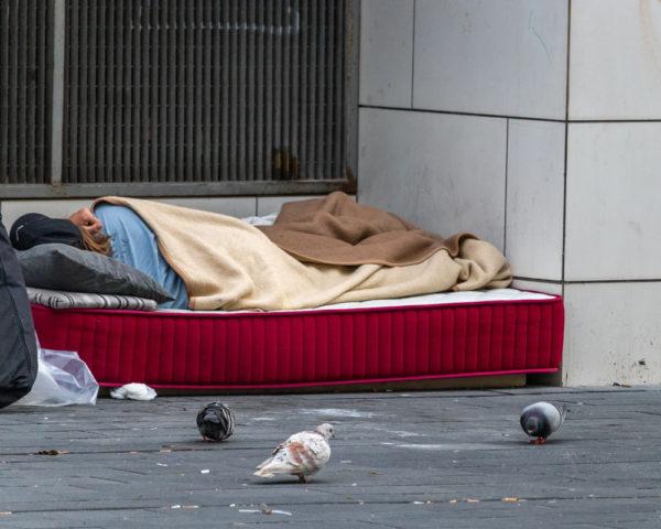 Homeless woman sleeping on mattress in spain