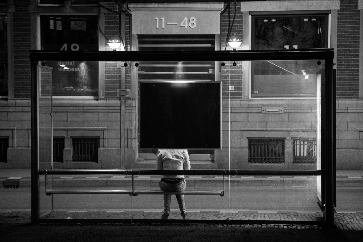 woman sits at bus stop