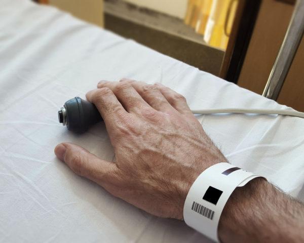 sick person's hand on nurse button