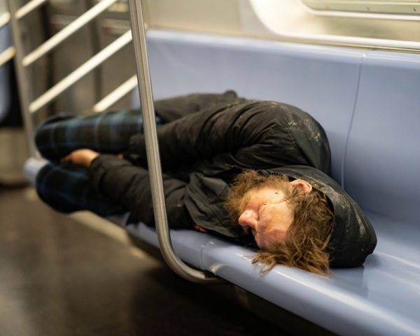 a homeless man sleeps on a NYC subway bench during Coronavirus