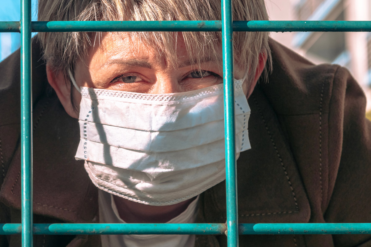 woman wearing face mask behind bars