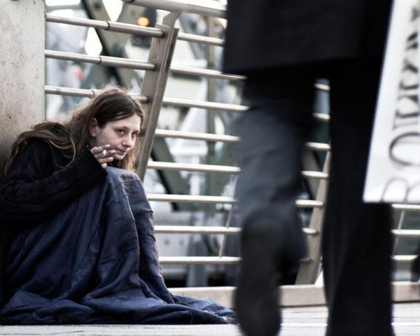 homeless woman smokes a cigarette