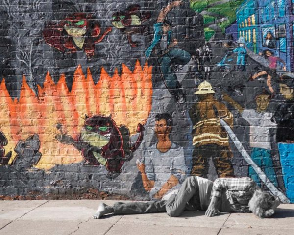 homeless person sleeps in front of San Francisco Mural