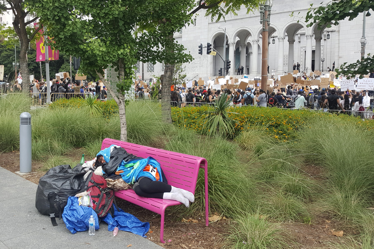 homeless woman sleeping on bench during LA protest