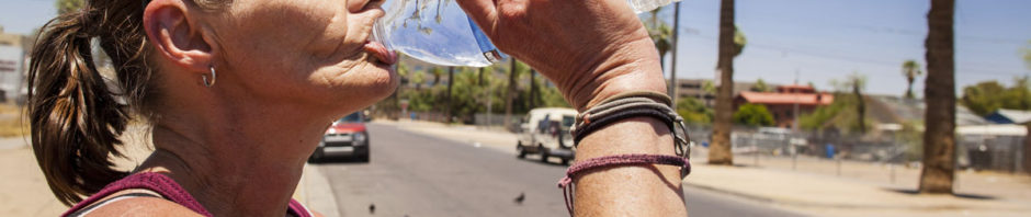 homeless woman drinks from a bottle of water in Phoenix, AZ