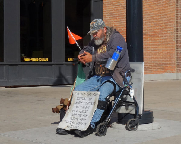 a homeless veteran sits on the street with a sign