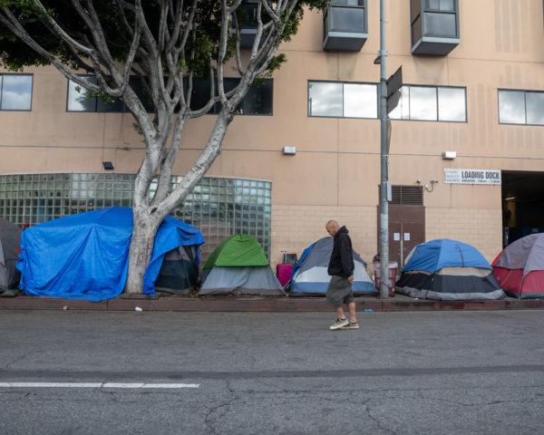 a man walks by a homeless encampment in LA