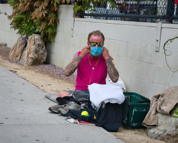 homeless man puts on his coronavirus mask