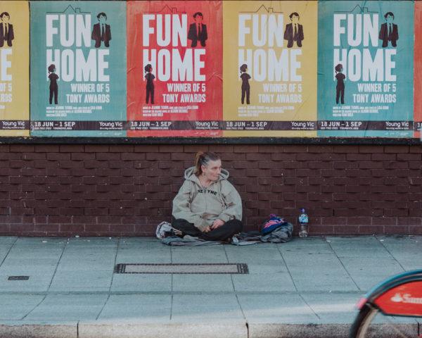 homeless woman sits on a sidewalk in London