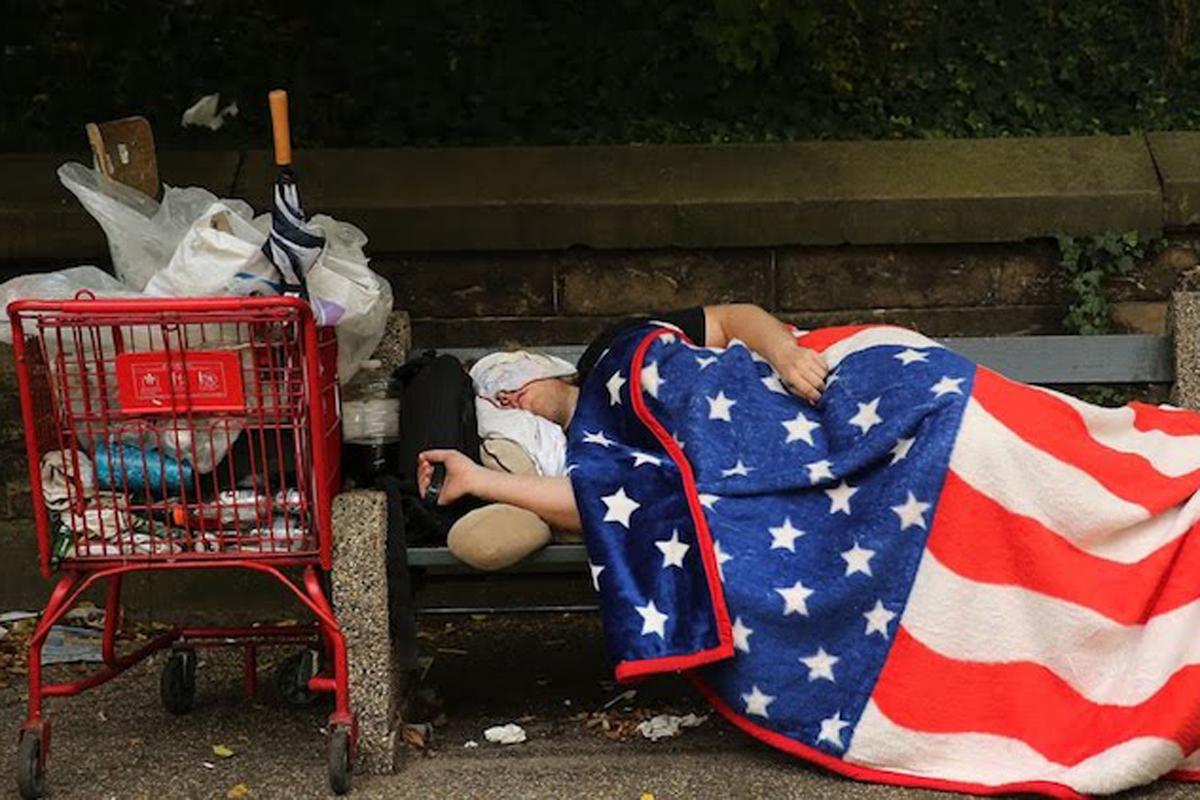homeless woman sleeping on a park bench