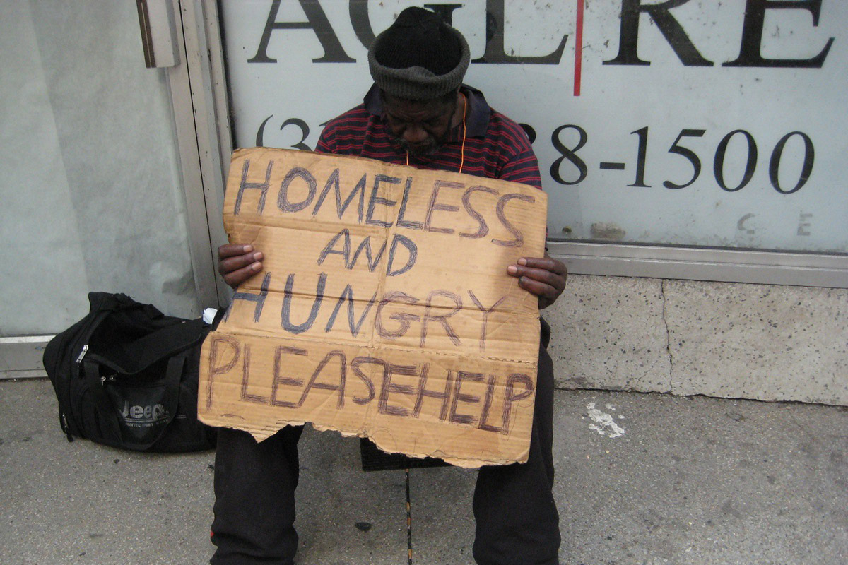 man holds homeless and hungry sign