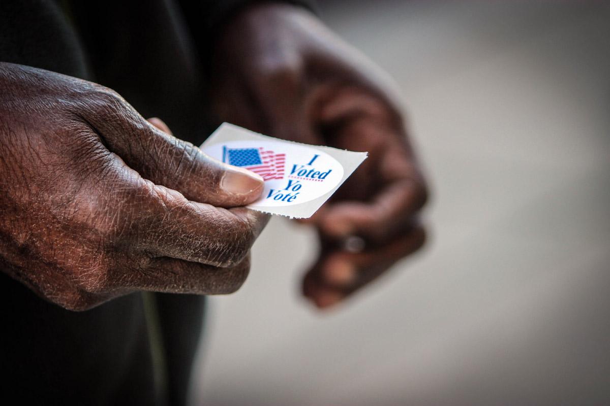 elderly man holds vote sticker