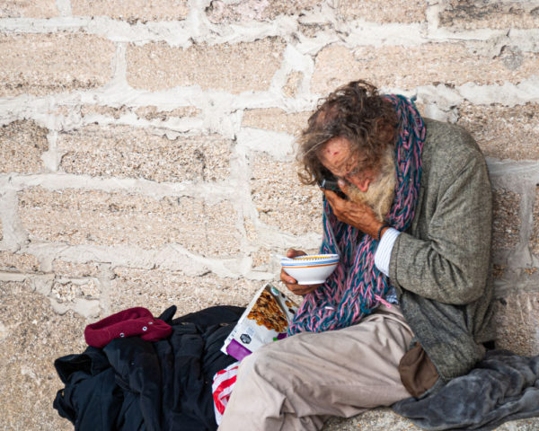 elderly homeless man uses his cellphone