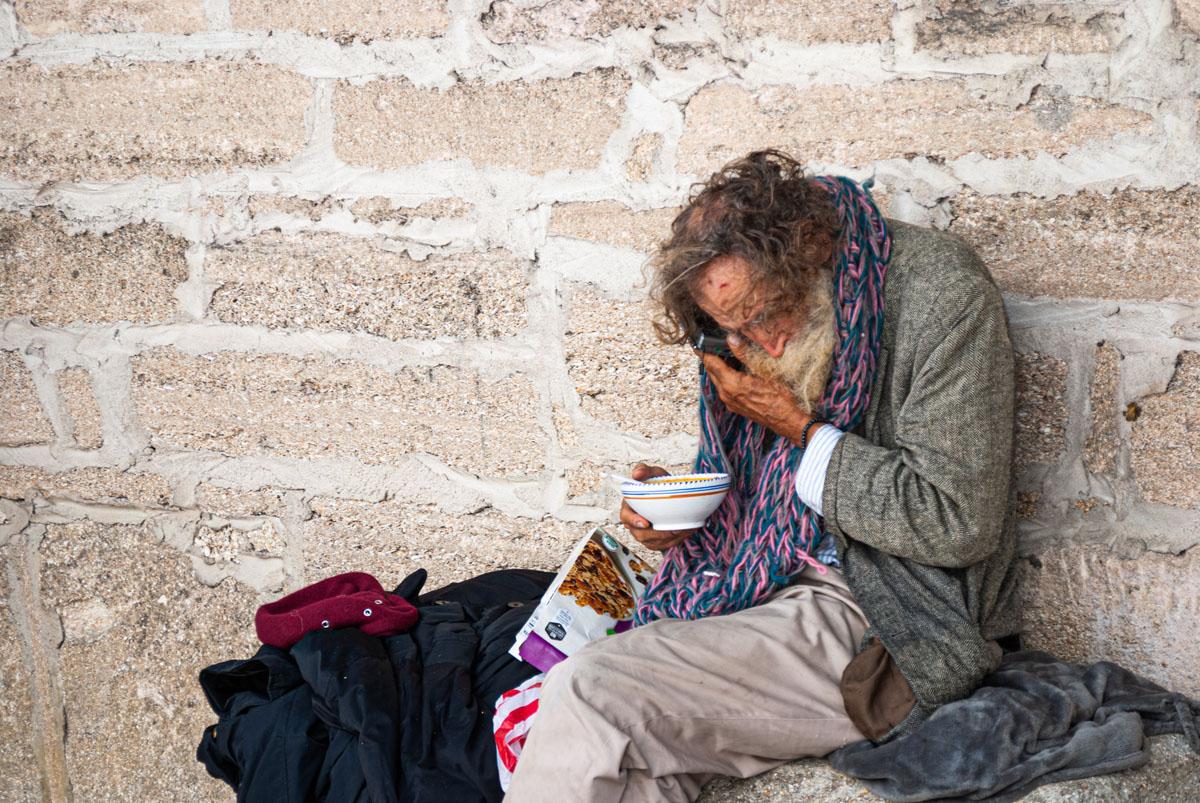 elderly homeless man uses his cellphone