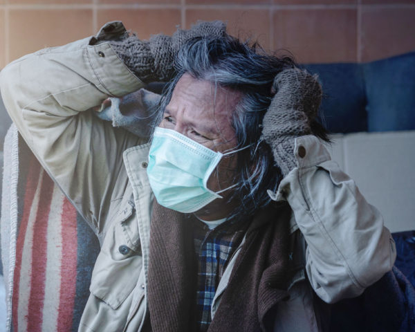homeless man putting on a mask